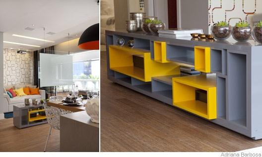 Servindo como divisor de ambientes (sala de jantar e sala de TV) e para guardar os equipamentos de home-theater, o móvel com vazados em cinza incorporou os nichos amarelos. Projeto de Adriana Fontana.