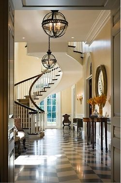 Drop dead gorgeous foyer by architect Allan Greenberg and interior design firm Cullman Kravis. Deep longitudinal space has a surprising setback spiral staircase, as opposed to the more obvious traditional staircase with a landing off to one side. Two black orb chandeliers one behind the other lead your eye through the space, as do the french doors at the end of the hall. Stunning millwork and black and white marble floor.