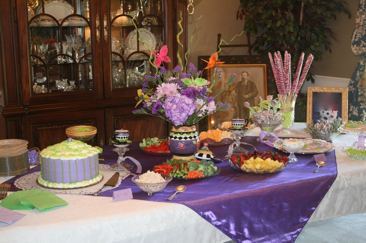 """Purple and green baby shower!  A Purple """"cupcake"""" cake was the center of the table. Green and purple candy sixlets in bowls and large purple and white suckers  in green plastic beads added to the decor.  Cups were glued on to clear candle holders with purple votive candles inside.  Cookies were frosted then decorated with green and purple butterflies. A quick table cloth topper was made with a few yards of fabric and sewn. tablecloth"""