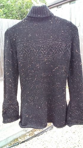 This figure-hugging jumper is knitted with your choice of either no or negative ease to the body, bearing in mind there is some stretch and give in the finished fabric. In contrast the sleeves open out into a bell shape at the cuff to give an interesting twist to the garment. The lace panel that crosses the yoke is repeated just about the cuff whilst the gently curled edges give the whole jumper a soft edge. It is finished with a polo neck that adds further sleekness to the whole effect.