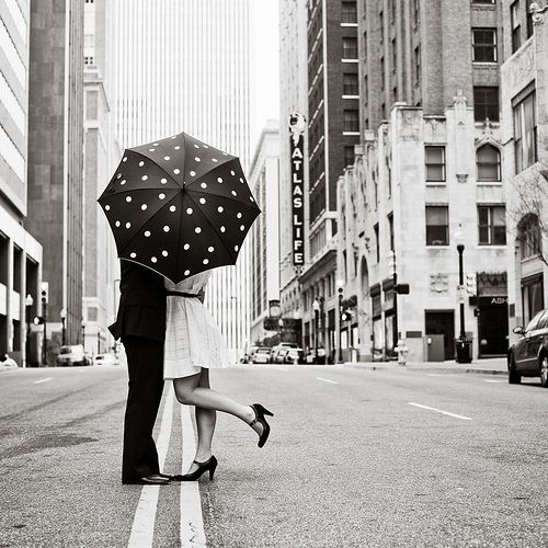 A polka dot umbrella covers the Bride and Groom kissing. Cute idea for it it is raining