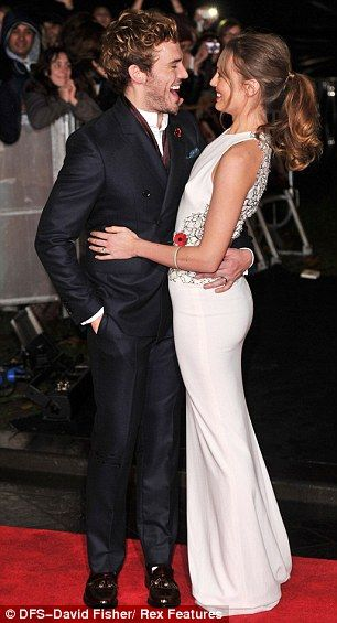 Celebrity couple Sam Claflin and wife Laura Haddock share a romantic giggle on the red carpet. via dailymail.co.uk