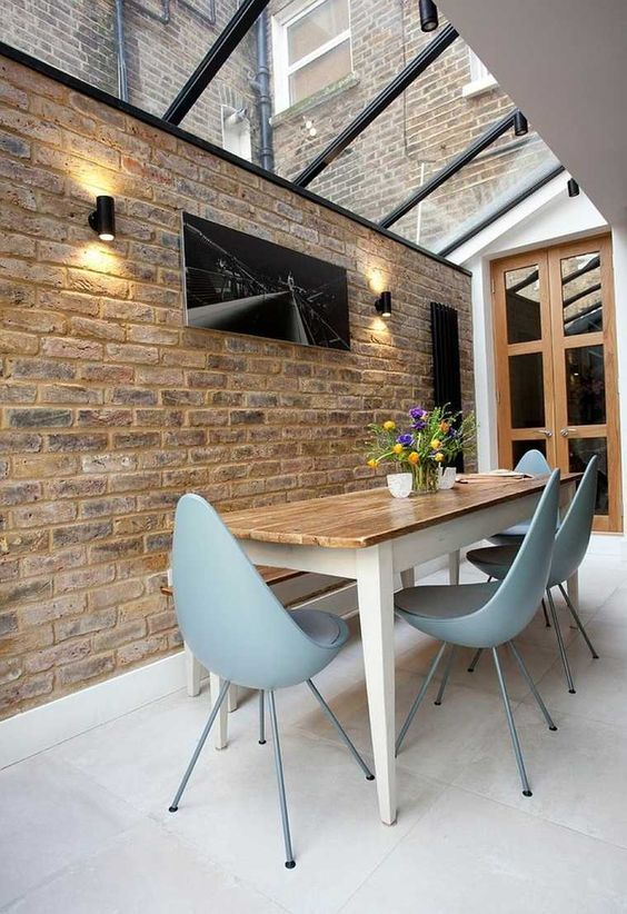 Modern dining room with glass ceiling, brick wall and excellent blue chairs.