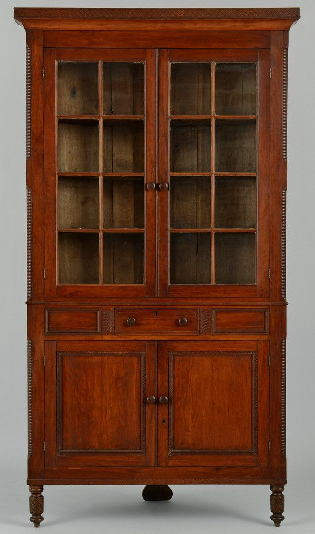 """East Tennessee cherry corner cupboard, attributed to McMinn County. Illustrated in The Art & Mystery of Tennessee Furniture by Harsh & Williams, p. 187, fig. 231. Ogee cornice with incised diamond design over two doors with twelve glazed panes, straight back side returns, ring-turned molding to case corners, center drawer flanked by foliate carved designs on each side & panels with incised moldings flanking central drawer... 94 1/8"""" H x 47 3/4"""" W x 20"""" D. 2nd quarter of the 19th century."""