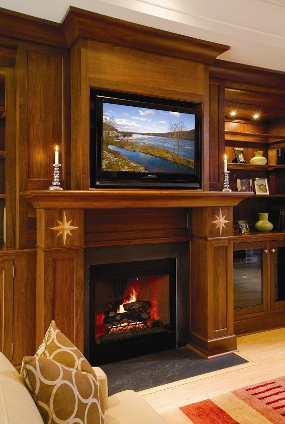 these built in book shelves and center with a fireplace surround by superior woodcraft are crafted of walnut and finished with a handruu2026