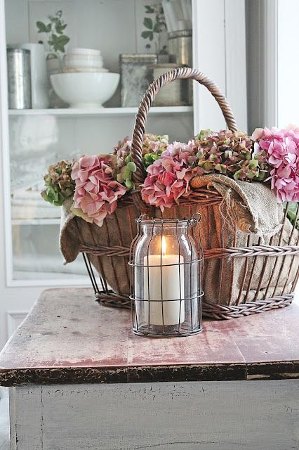 Simple pretty touches like baskets of flowers and candles in jars work perfectly with summer house style