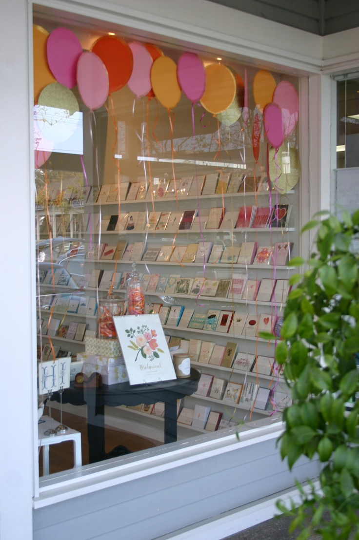 What a happy window display border! Balloons cut from paper (note the edges are highlighted and LOTS of dangly curly ribbon!) TGtbT.com can see this for spring, any celebration including New Year's, kidswear windows, even (in yellow and red) as SALE balloons!