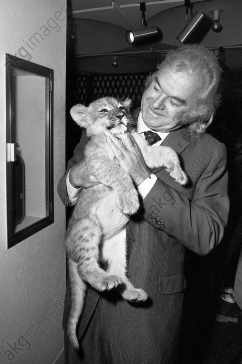 Johnny Stark (1922–1989), manager de Mireille Mathieu avec un lionceau que le comte Paul de La Panouse, propriétaire du zoo de Thoiry, apprivoisa et qu'offrit Mireille Mathieu à la Chahbanou Farah Diba Pahlavi lors d'une tournée internationale, 1969