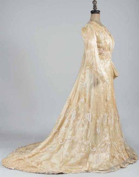 Tea-gown à ligne Princesse vers 1900. Robe d'une pièce en satin duchesse crème voilé de tulle brodé en relief de glycines et volutes blanches, pois et fleurettes en Cornely ton sur ton. Robe baleinée à traine et volant balayeuse.