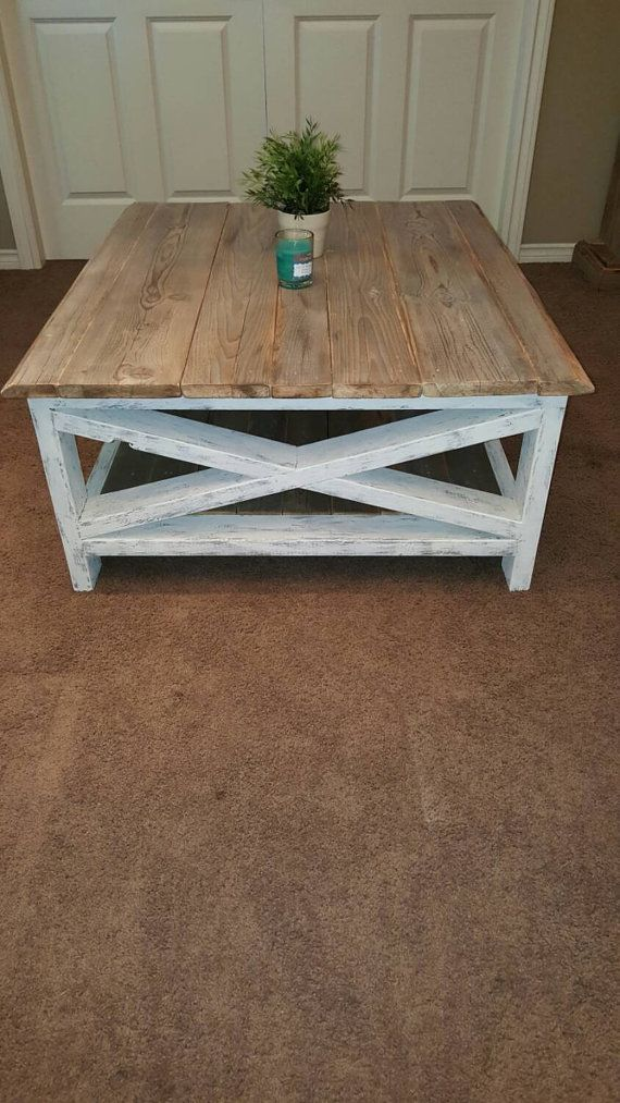 This distressed white coffee table is made with reclaimed wood found in the Okanagan Valley in B.C. Canada. The top and middle shelfs are