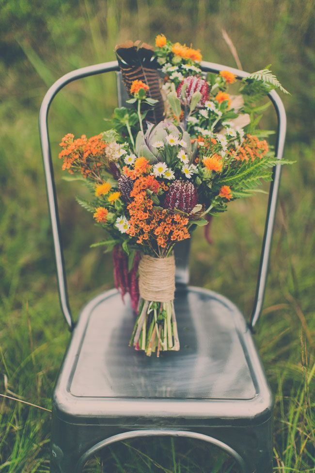 African vibed wildflowers in hues of purple, orange & green | Exotic Bohemian Chic Wedding In A Private Prairie Setting | Photograph by Memories n More  http://storyboardwedding.com/exotic-bohemian-chic...