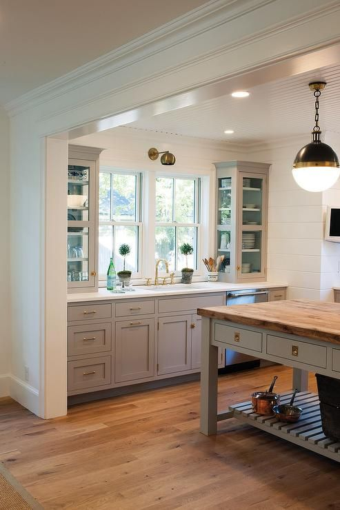 Amazing kitchen with light gray cabinets painted Farrow & Ball Dove Tale paired with a white quartz countertop.