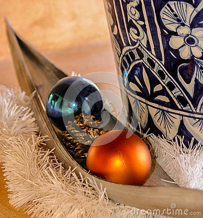 Painted blue and white vase with a boat shaped vessel with two Christmas balls and a pine cone.