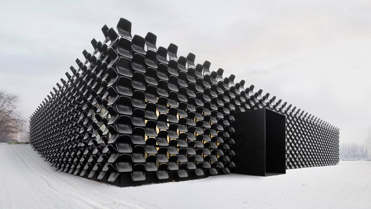 Hundreds of used black plastic chairs cover the facade of this furniture shop by architecture studio Chybik + Kristof in the Czech city of Brno