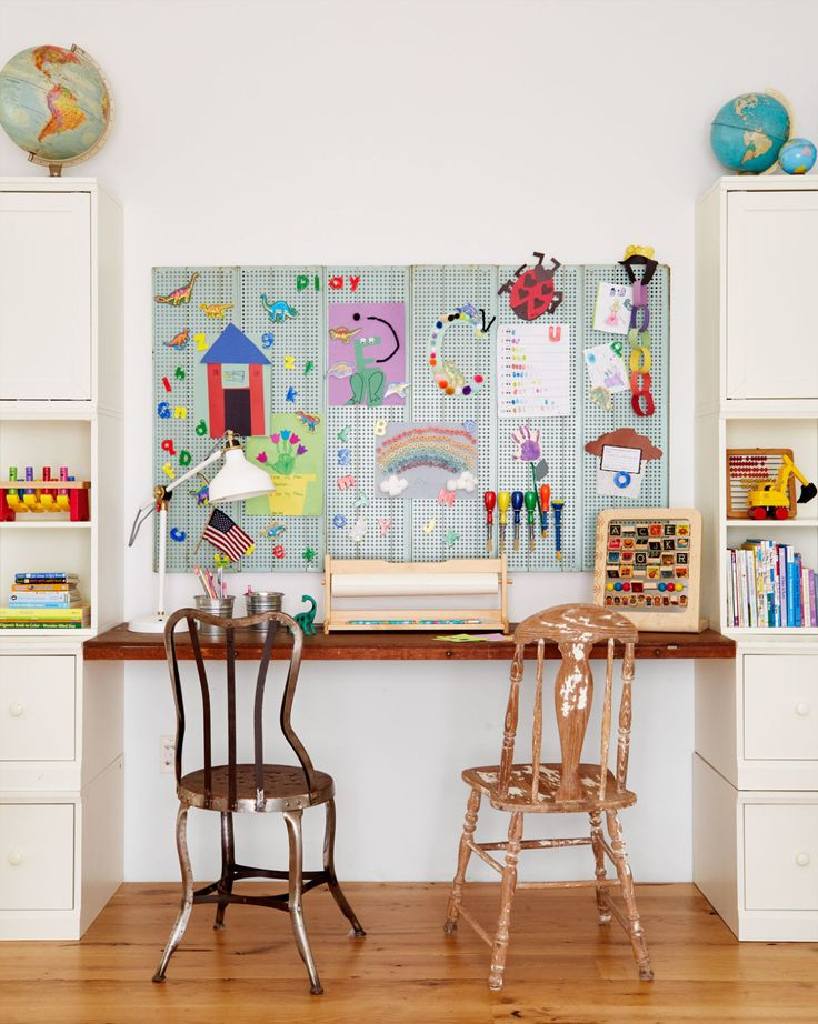 Modern farmhouse style kids playroom. This kids' space is as creative as the pint-size crafters who use it. To eek out every last inch in this nook, Lauren made a desk by floating the top of an antique wallpaper prep table between two white bookcases. Just above, a magnetic mint green shelf from an old pharmacy serves as a happy backdrop for mini masterpieces.