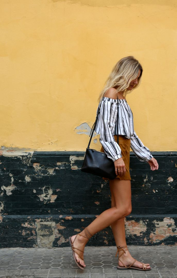 Striped blouse paired with that quintessential tan suede skirt we're seeing everywhere. The black leather bag balances out the colour palette in this outfit.
