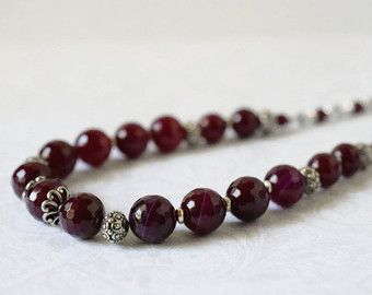 Ruby Red Tiger Eye Necklace Marsala Red Necklace Garnet Stone Necklace Statement Beaded Gemstone Necklace Sterling Silver Burgundy Handmade  This handcrafted garnet or ruby red tiger eye necklace is adorned with semi precious tiger eye gemstones in a pretty marsala red hue. High quality tiger eye gemstones beautifully polished round faceted gemstones. The center focal point is a pretty antique silver hammered tube bead set with antique silver beaded square links, and antique silver beads…