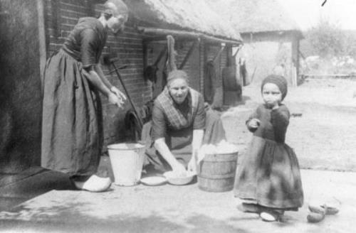 Vrouwen zijn buiten, naast het huis, aan het werk, een jongetje staat erbij. | Collectie Gelderland Foto opgenomen in G. van den Brink, Hierdense herinneringen, 1981, blz. 79. Het bijschrift luidt: 'Een jongetje in rokken. Van links naar rechts: Eibertje Beelen-Hop, haar schoonmoeder Griet Brandsen en haar zoontje Hendrik, die nog een rok draagt. Een vredig tafereeltje uit omstreeks 1929.' Stadsmuseum Harderwijk #Gelderland #Veluwe #oudedracht