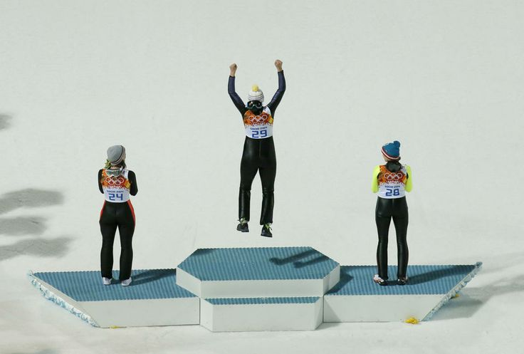 Vogt wins 1st gold medal in Olympic ski jumping - Germany's gold medal winner Carina Vogt jumps onto the podium as she is flanked by Austria's silver medal winner Daniela Iraschko-Stolz, right, and France's bronze medal winner Coline Mattel during the flower ceremony of the women's normal hill ski jumping final at the 2014 Winter Olympics, Tuesday, Feb. 11, 2014, in Krasnaya Polyana, Russia.(AP Photo/Dmitry Lovetsky)