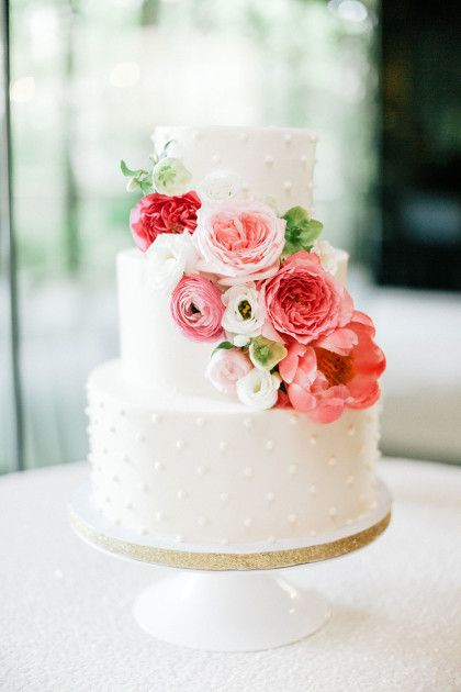 Swiss dots 3 tiered wedding cake with butter cream cake adorned with fresh florals. Love love