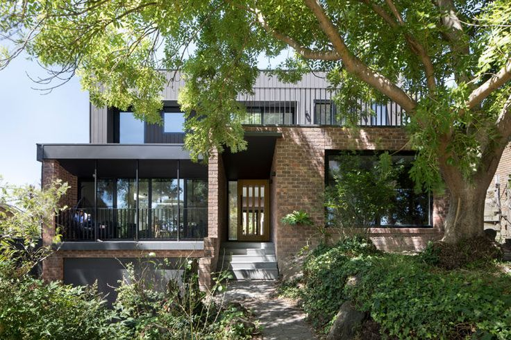 Inbetween Architecture have designed the modern renovation of a 1970's double storey brown brick house near a park in Melbourne, Australia, that's home to a family of 5 that have outgrown the home.