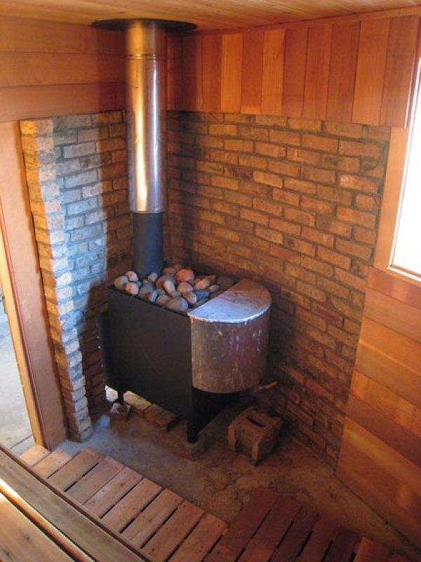 Here's a charming sauna stove in the corner of a DIY sauna.