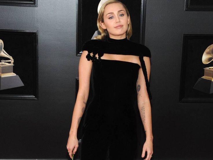 """Ein schwarzer Jumpsuit, ein Schal um die Schultern und romantische blonde Locken: Miley Cyrus zeigte bei den Grammys ihren neuen Look. Kurze Haare, rausgestreckte Zunge und freizügige Outfits: So präsentierte sich Miley Cyrus (25, """"Younger Now"""") gerne in den vergangenen Jahren..."""