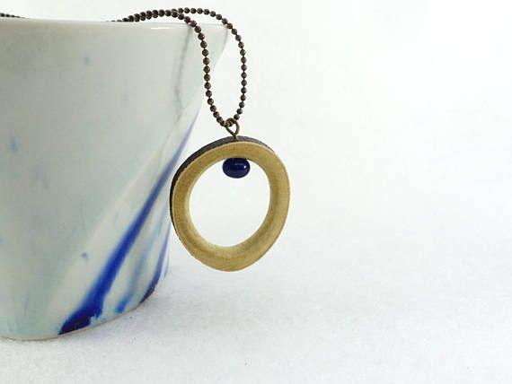 Pendentif anneau de bois simple et perle en verre bleue