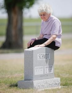 Sarah Schmidt, 81, sits on the tombstone of her husband, Harold, who died from injuries he sustained in the 2007 Greensburg tornado. Schmidt...