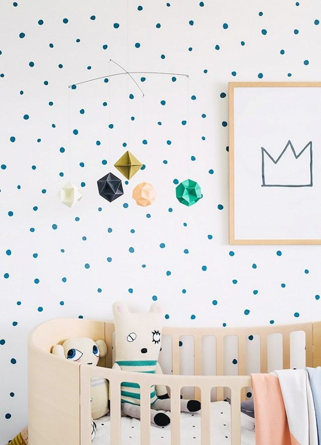 Gender-neutral nursery with printed wallpaper, a modern mobile, and a wooden crib