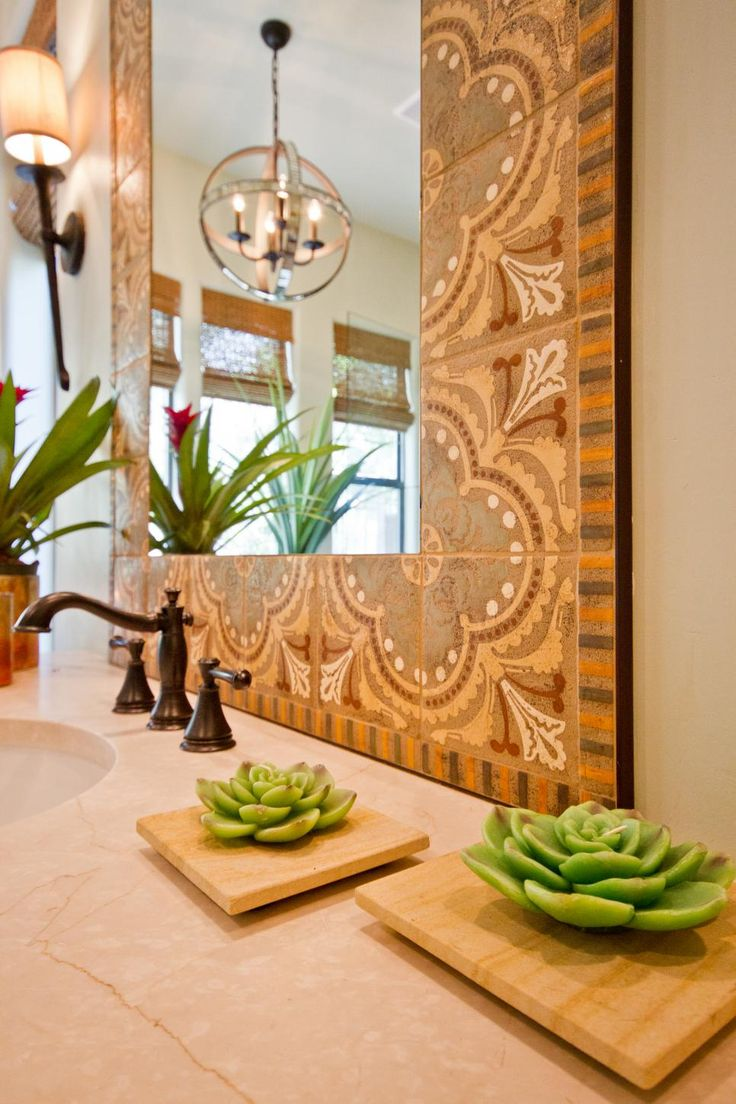 Ornamental tile surrounding the mirror adds a beautiful design detail to this southwestern bathroom. A brushed bronze faucet stands out against the light countertop and succulent-shaped candles add a refreshing pop of green.