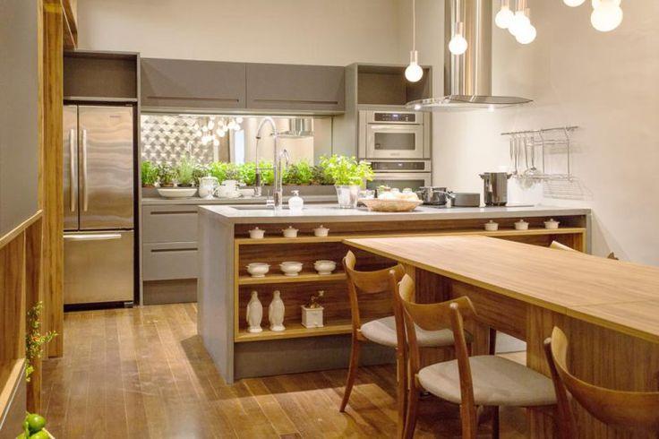 Mary Oglouyan assina esta cozinha, que investe na paleta de grafite e concreto para afirmar a sofisticação. A madeira é elemento-chave, com destaque para a mesa de laminado com 12 lugares, encaixada na ilha com cooktop, prateleiras e pia. Na parede lateral, a estante serve tanto à cozinha como à sala, recebendo inclusive a TV e a lareira.