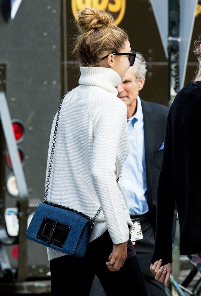 Gigi Hadid wears a white turtleneck seater with a denim chain-strap bag by Tom Ford