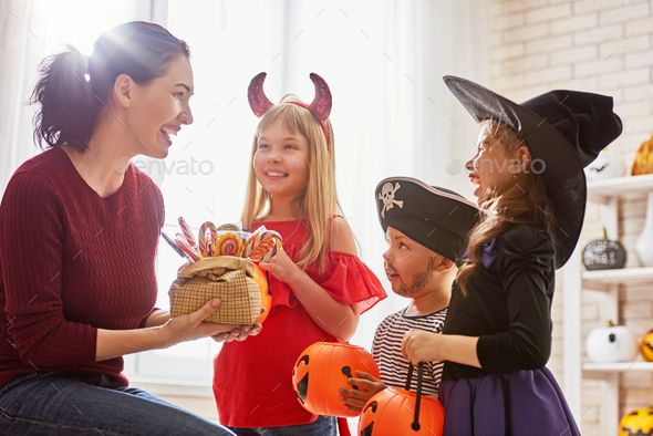 Family Celebrating Halloween By Choreograph Happy Family Celebrating Halloween Young Mom Treats Children With Candy Funny Kids In Halloween Photos Funny Kids Halloween