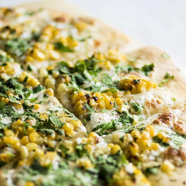 This easy homemade cilantro corn pizza recipe is perfect for summertime! Sweet corn, fresh cilantro, gruyere cheese and fresh mozzarella. Vegetarian.