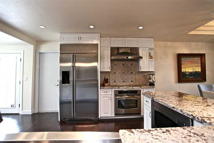 stainless steel appliances, granite countertops, white cabinets ...