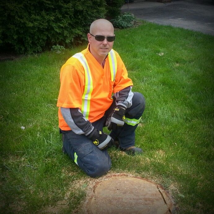 Picture of me with my safety gear, chainsaw pants, Stihl steel toe shoes and visible shirt. Nice birch tree cut flush with the grass, another happy customer