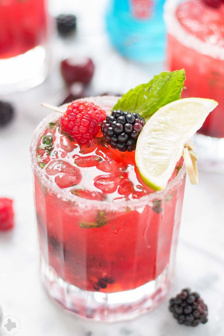 A hybrid between a mojito and a classic martini, this Triple Berry Mojitini is patriotism in a glass. Muddled mint, sugar and berries combine with limeade and Smirnoff Red White and Berry to bring you this refreshing cocktail perfect for all your outdoor parties! | Strawberry Blondie Kitchen