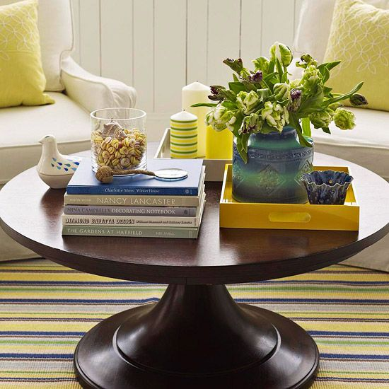 Coffee tables offer lots of space for books, flowers, and decorative pieces. To keep objects orderly and pleasing to the eye, use trays to group similar items, such as ceramics and pillar candles. Try clustering candles of different sizes and colors in one tray and bowls or vases in another. Then jazz up a stack of books by topping with a vessel filled with found objects.