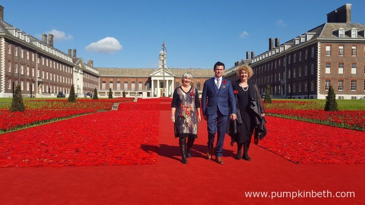 Designer Phillip Johnson and his team with their installation of nearly 300,000 knitted and crocheted poppies, to commemorate the 100 years of warfare since the First World War.
