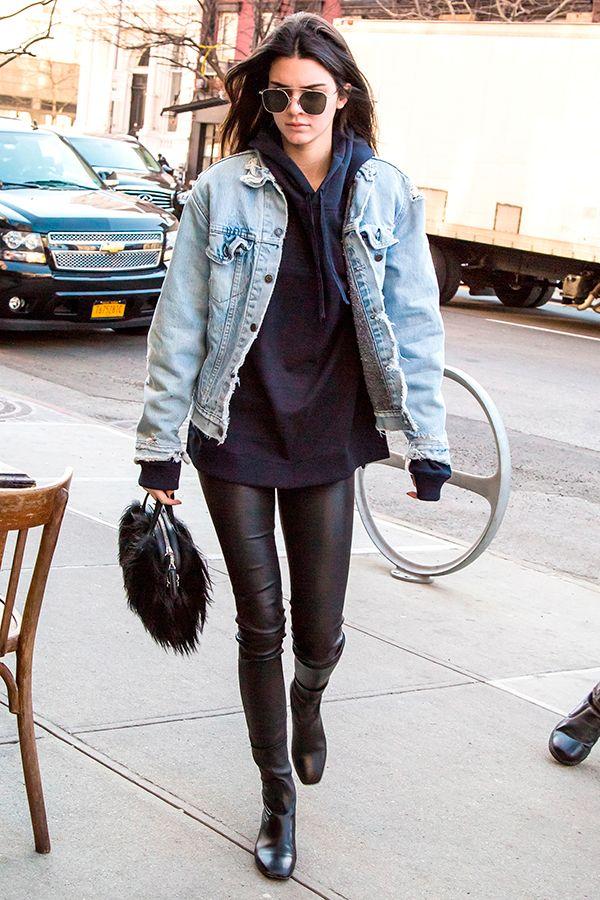 Kendall Jenner usa jaqueta jeans com moletom com calça de couro e botas pretas