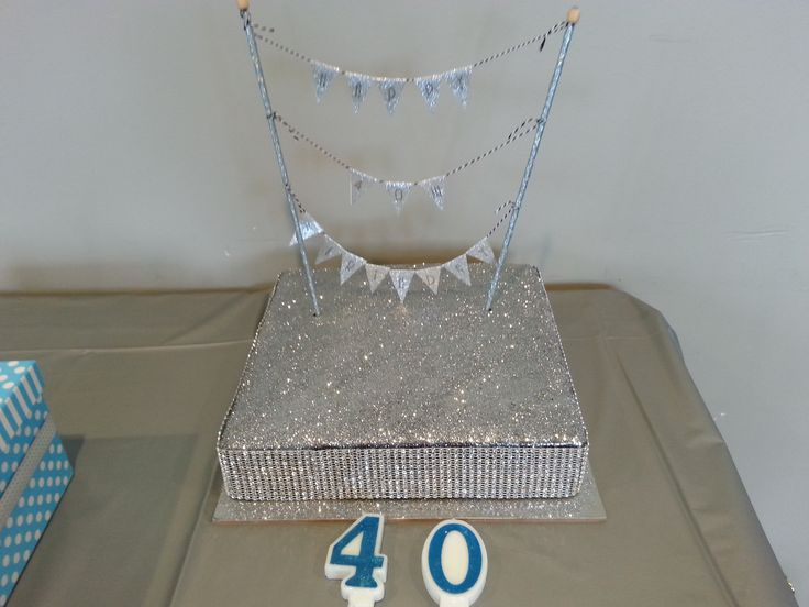 This was my cake I decorated for my Flashy 40th birthday. We were on holidays so I ordered a Michel's patisserie mud cake and covered it with silver glitter from the cake shop, then put a diamante ribbon around the bottom. I make the bunting myself. It turned out well and tasted even better. The glitter added a little bit of crunch to the cake which the guests loved.