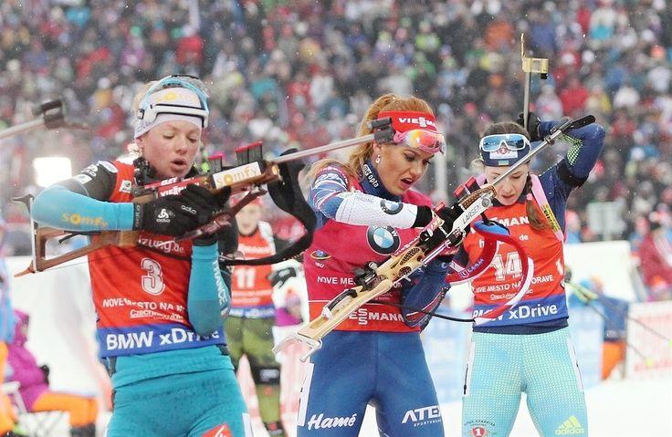 NA STŘELNICI. Gabriela Koukalová (uprostřed) si připravuje malorážku ke střelbě.