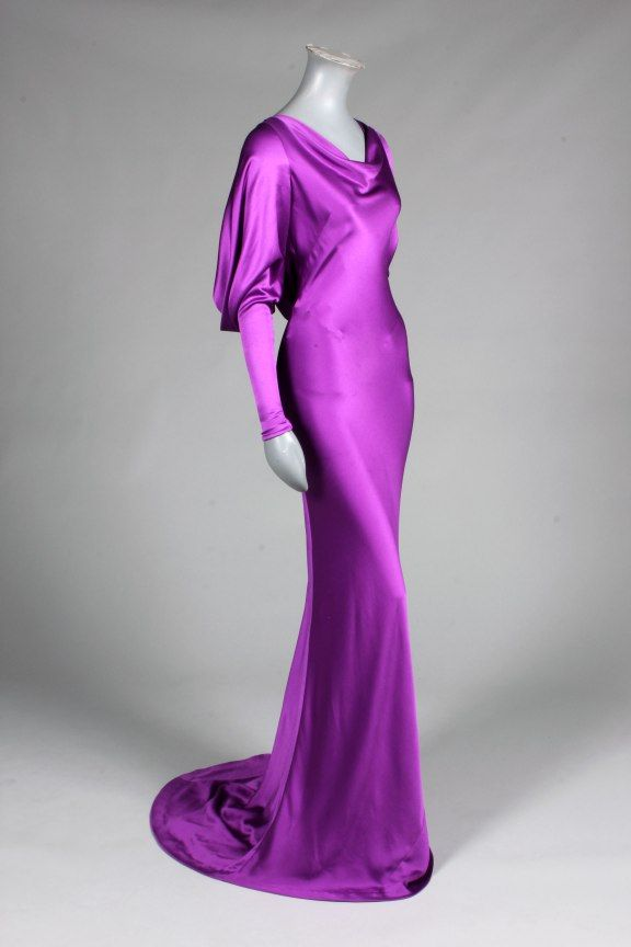 Alexander McQueen purple satin evening gown, with cowl neck, draped dolman sleeves with narrow zippered cuffs, bias cut skirt with fish-tail hem, spaghetti strap to the low back opening which catches the draped swags which fall from the shoulders