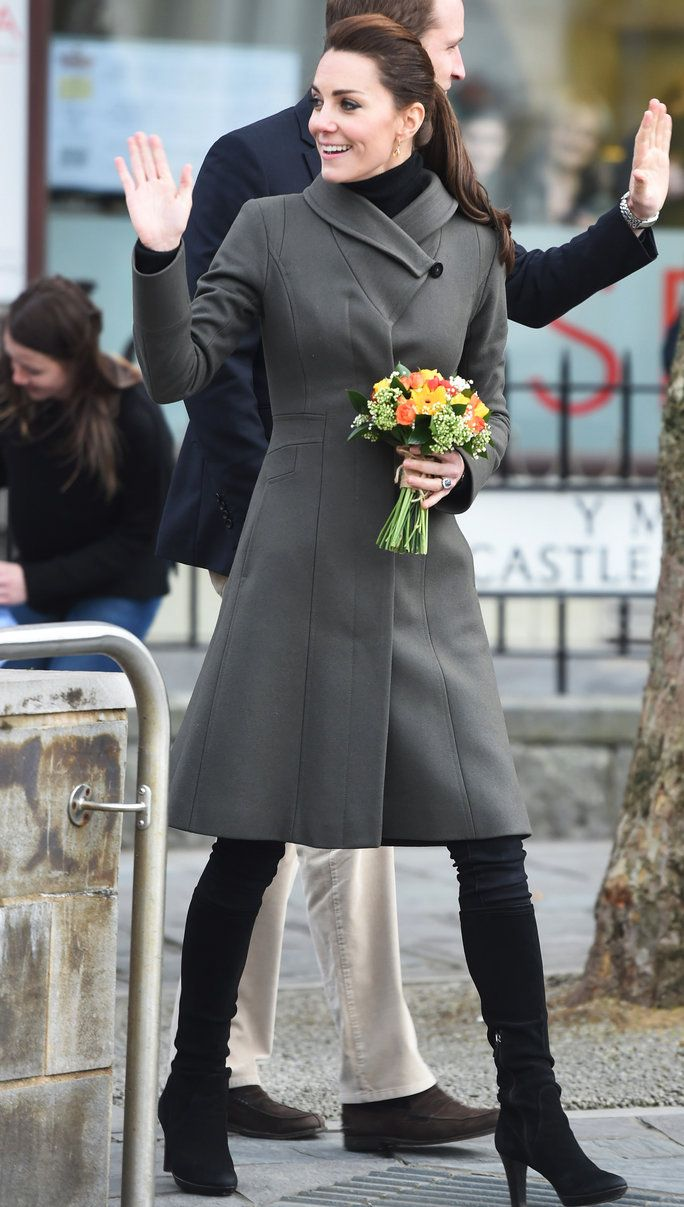 Kate Middleton in a gray, knee-length coat in Caernarfon Castle Square to greet the leaders of philanthropic organizations like Mind UK and GISDA.
