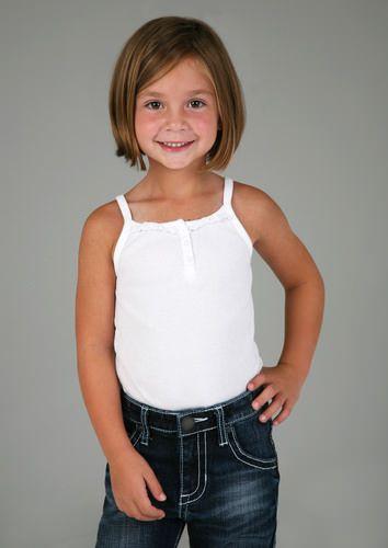 Cette fillette porte une jolie coupe de cheveux au carré, séparés sur le côté. Une longue frange traverse son front.