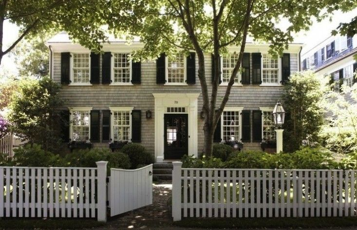 gray colonial house with black shutters and white picket fence, Gardenista