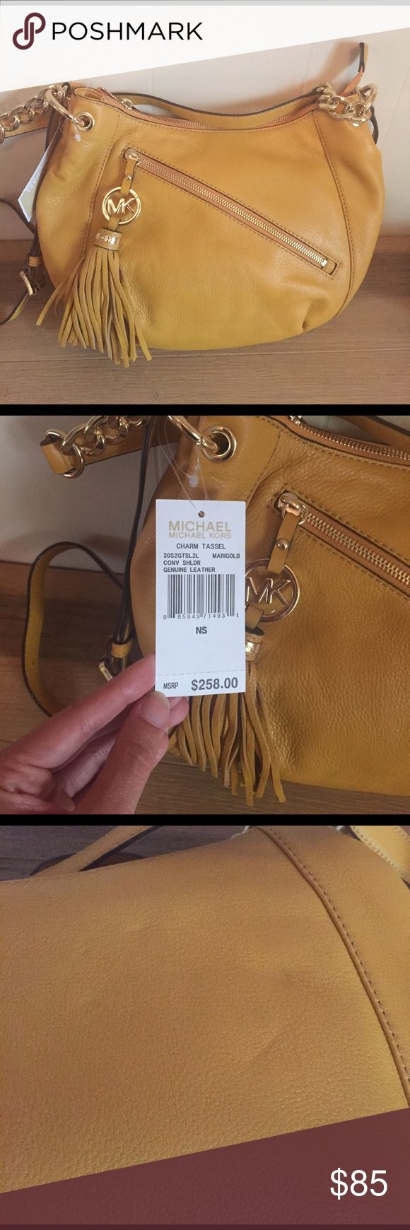 Michael Kors charm tassel purse Brand new with tags. Color is marigold. Has an adjustable cross body strap as well as handles. Comes with a Dustbag. Slight scuffing due to storage. Price firm Michael Kors Bags Crossbody Bags