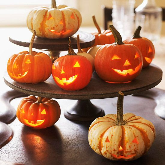 To get this look, arrange miniature jack-o'-lanterns on footed cake stands! More #centerpiece ideas: http://www.bhg.com/halloween/indoor-decorating/quick-clever-halloween-centerpieces/
