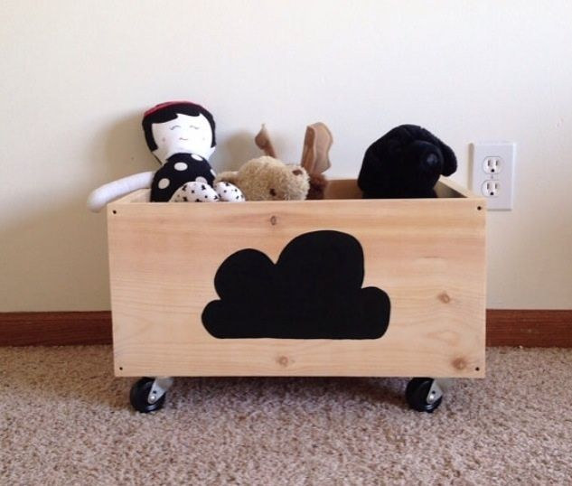 """The toy and teddy crate is a perfect storage solution for toys, teddies, blankets and books. This solid wood crate sits on 2"""" swivel caster wheels. My kids love how easy it is for them to roll it from room to room for easy play (and I like that it's easy for my kids to roll back for fast clean up). Crate comes with the front side painted with a simple cloud design. Approx 19.5"""" across x 13"""" deep x 12"""" floor to top"""